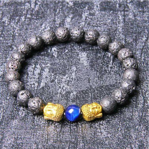 Bracelet pierre de lave avec deux têtes de bouddha dorées et une perle bleu sur fond gris