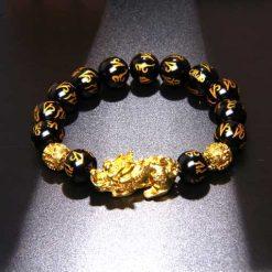 Bracelet om mani padme om avec symbole dragon pixiu en perles d'obsidienne naturelle sur fond noir