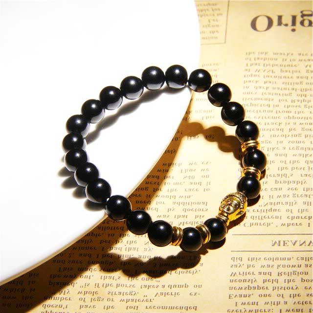 bracelet en perles obsidienne et tête de bouddha dorée