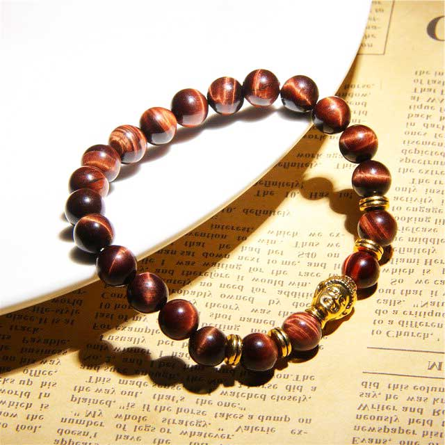 bracelet en perles d'œil de taureau et tête de bouddha dorée